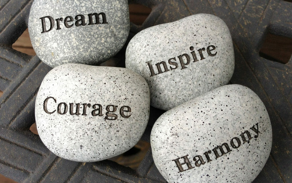 "Four rocks that have the words ""Dream"", ""Inspire"", ""Courage"" and ""Harmony"" printed on them."