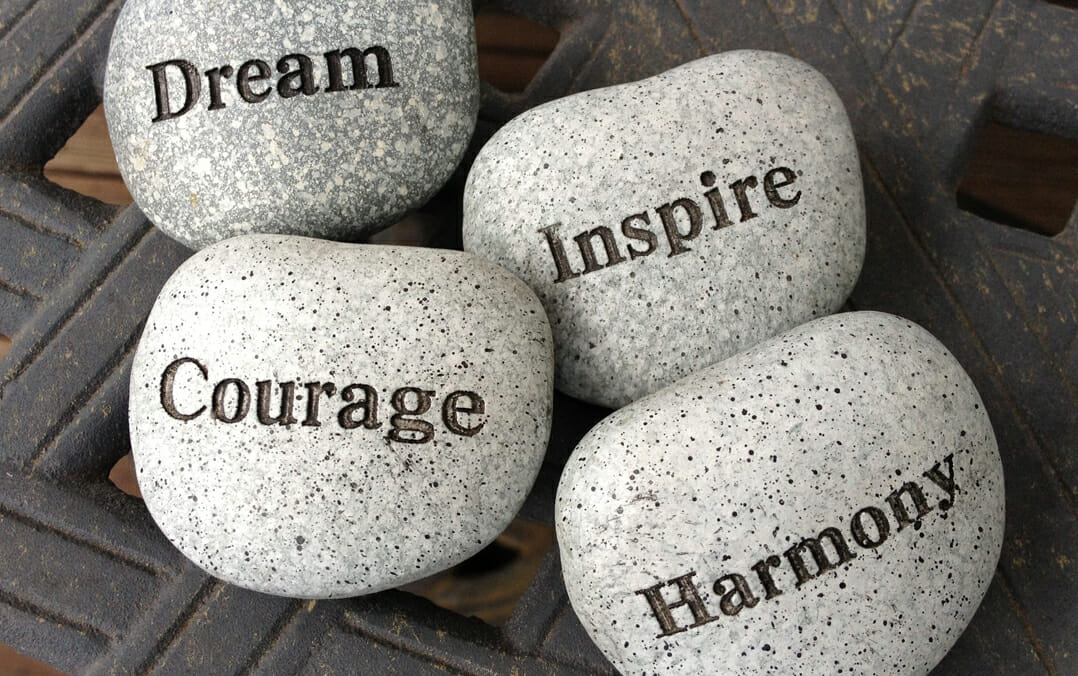 """Four rocks that have the words """"Dream"""", """"Inspire"""", """"Courage"""" and """"Harmony"""" printed on them."""